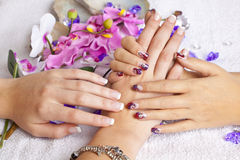 Beauty concept - acrylic fingernails. A beauty concept - hands with acrylic fingernails, flowers, shells and crystals stock image