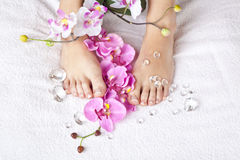 Beauty concept - acrylic toenails. A beauty concept - feet with acrylic toenails, flowers and crystals royalty free stock photo