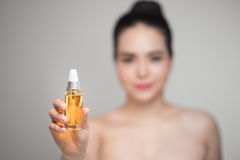 Beauty concept. Asian pretty woman with perfect skin holding oil. Bottle Stock Photos