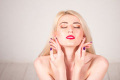 Beauty concept. Beautiful woman with blond straight hair and red lips touching her skin. Manicure. Beautiful woman with blond straight hair and red lips touching Royalty Free Stock Photo