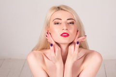 Beauty concept. Beautiful woman with blond straight hair and red lips touching her skin. Manicure. Beautiful woman with blond straight hair and red lips touching Royalty Free Stock Images