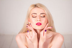 Beauty concept. Beautiful woman with blond straight hair and red lips touching her skin. Manicure. Beautiful woman with blond straight hair and red lips touching Royalty Free Stock Image