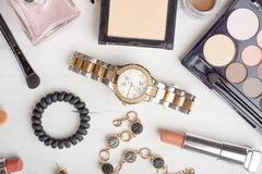 Beauty concept in a blog. Professional female make-up accessories: watches, bracelet, lipstick, brush, powder, on a marble stock image