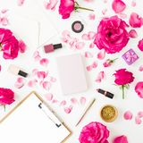 Beauty concept with cosmetics - lipstick, eye shadows, nail polish, pink roses and clipboard and notebook on white background. Fla. T lay royalty free stock images