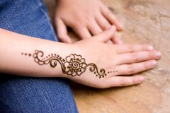 Henna tattoo on small girl hand. Mehndi is traditional Indian decorative art. Close-up, overhead view - beauty concept. Beauty concept - henna tattoo on small royalty free stock photography