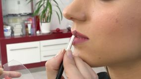 Beauty concept. Makeup artist doing face make up to young woman stock footage
