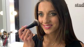 Beauty concept. Makeup artist doing face make up to young woman stock video footage