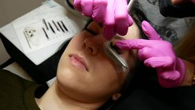 4K Beauty concept. The master of eyelash extension in pink gloves lengthens eyelashes client. Beautician checks the. Beauty concept. The master of eyelash stock video