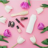 Beauty concept with shampoo, combs, cosmetics and flowers on pink background. Flat lay, top view. Beauty concept with shampoo, combs, cosmetics and flowers on Stock Photography