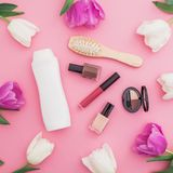 Beauty concept with shampoo, combs, cosmetics and flowers on pink background. Flat lay, top view. Beauty concept with shampoo, combs, cosmetics and flowers on Stock Image
