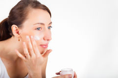 Beauty concept. Skin care. Beautiful Woman putting face cream on Stock Image