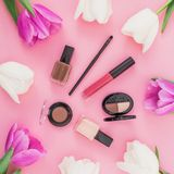 Beauty concept with tulips flowers and cosmetics on pink background. Top view. Flat lay. Home feminine desk. Beauty concept with tulips flowers and cosmetics on royalty free stock image