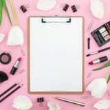 Beauty concept with white flowers, clipboard, cosmetics and accessory on pink background. Top view. Flat lay. Home feminine desk. Beauty concept with white stock photos