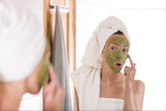 Beauty concept. The woman applies green organic face mask in the bathroom royalty free stock photography