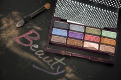 Beauty cosmetic. Words beauty write on black with colorful eyeshadow Royalty Free Stock Photos