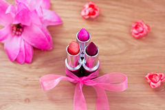Beauty cosmetics: lipsticks, bow and flowers Stock Photo