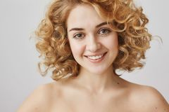 Beauty and cosmetology concept. Close-up portrait of attractive curly haired woman with bright kind smile standing naked stock photography