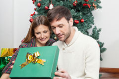 Beauty couple opening a christmas gift Royalty Free Stock Photo