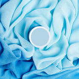 Beauty cream box over turquoise cloth. Healthcare concept. Beauty cream box over turquoise vapory and wavy cloth background Royalty Free Stock Image