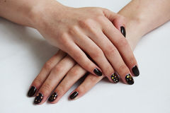 beauty delicate coffee manicure with gold sparkles with gel varnish on a white wall background Royalty Free Stock Photography