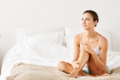 Beautiful woman with bare legs on bed at home stock photo