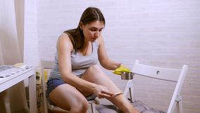 Beauty, depilation, epilation, hair removal and people concept - beautiful woman with applicator applying depilatory wax. To her leg stock video footage