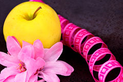 Beauty and diet: apple, flower, measuring tape. Apple, flower, measuring tape as symbols of dieting Stock Photo
