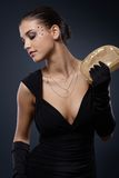 Beauty dressed for elegant party. Posing in black dress with golden party handbag and gloves, glamorous makeup with strasses Royalty Free Stock Photo