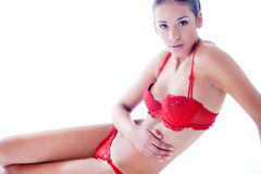 Beauty dressed in red lingerie sitting on the floo Royalty Free Stock Photography