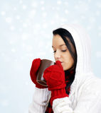 Beauty drinking hot beverage. Beautiful young woman drinking comforting hot chocolate, coffee or tea in mug held with red mittens on a cold snowy winter day Royalty Free Stock Photos