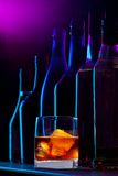 Beauty of drinks. Alcohol drink with ice and silhouette of the different bottles on dark background Stock Image