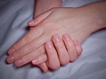 Beauty elegant female hands with manicure. Beauty elegant female hands with natural pink manicure on gray textured fabric Stock Images