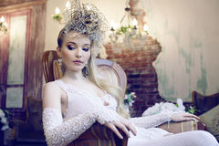 Beauty emotional blond bride in luxury interior. Dreaming, crazy complicate hairstyle Stock Photography