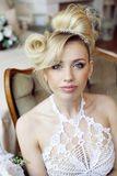 Beauty emotional blond bride in luxury interior. Dreaming, crazy complicate hairstyle Stock Photos