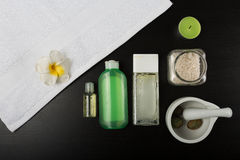 Beauty essentials. Beauty and spa treatment essentials on a dark wooden background Stock Image