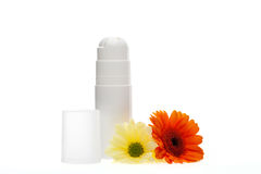 Beauty essentials. With two unlabelled white containers for skincare products alongside two colourful fresh Gerbera daisies on a white background Royalty Free Stock Photo