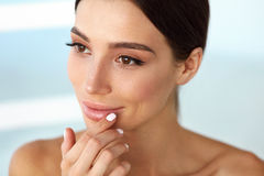 Beauty Face. Beautiful Woman Touching Lips With Lip Balm On Royalty Free Stock Photography