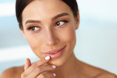 Beauty Face. Beautiful Woman Touching Lips With Lip Balm On Stock Photos