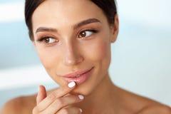 Beauty Face. Beautiful Woman Touching Lips With Lip Balm On Stock Photo