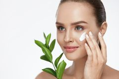 Beauty Face Care. Woman With Cream On Facial Skin. Beauty Face Care. Woman Applying Cream On Facial Skin Holding Green Plant On White Background. High Resolution Royalty Free Stock Images