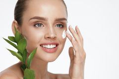 Beauty Face Care. Woman With Cream On Facial Skin. Beauty Face Care. Woman Applying Cream On Facial Skin Holding Green Plant On White Background. High Resolution Stock Photo