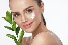 Beauty Face Care. Woman With Cream On Facial Skin. Beauty Face Care. Woman Applying Cream On Facial Skin Holding Green Plant On White Background. High Resolution Stock Image