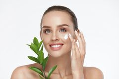 Beauty Face Care. Woman With Cream On Facial Skin. Beauty Face Care. Woman Applying Cream On Facial Skin Holding Green Plant On White Background. High Resolution Royalty Free Stock Photography