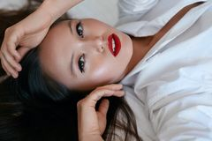 Beauty face makeup. Beautiful woman with black hair and red lips stock photos