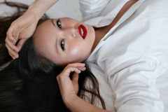 Beauty face makeup. Beautiful woman with black hair and red lips stock photography
