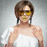 Beauty face portrait of sexy model with yellow sun glasses. Royalty Free Stock Photo
