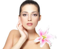 Beauty face of woman with flower. Beauty face of young woman with flower. Beauty treatment concept. Portrait over white background Stock Photography