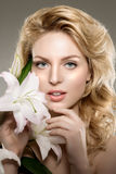 Beauty face woman, flowers, lily. Girl healthy model in spa salo. N. Cream treatment products. Facial skin terapy Stock Image