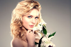 Beauty face woman, flowers, lily. Girl healthy model in spa salo Stock Photography