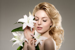 Beauty face woman, flowers, lily. Girl healthy model in spa salo Royalty Free Stock Photography